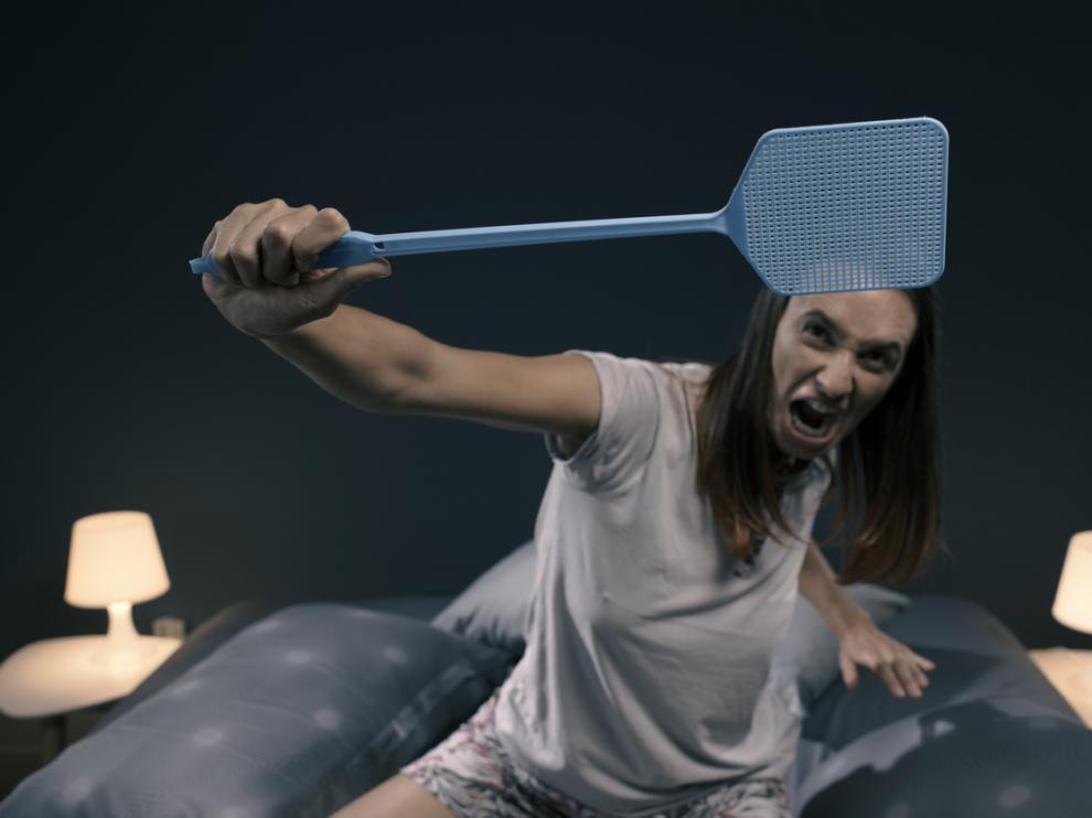 Mujer intentando matar moscas y mosquitos para poder dormir