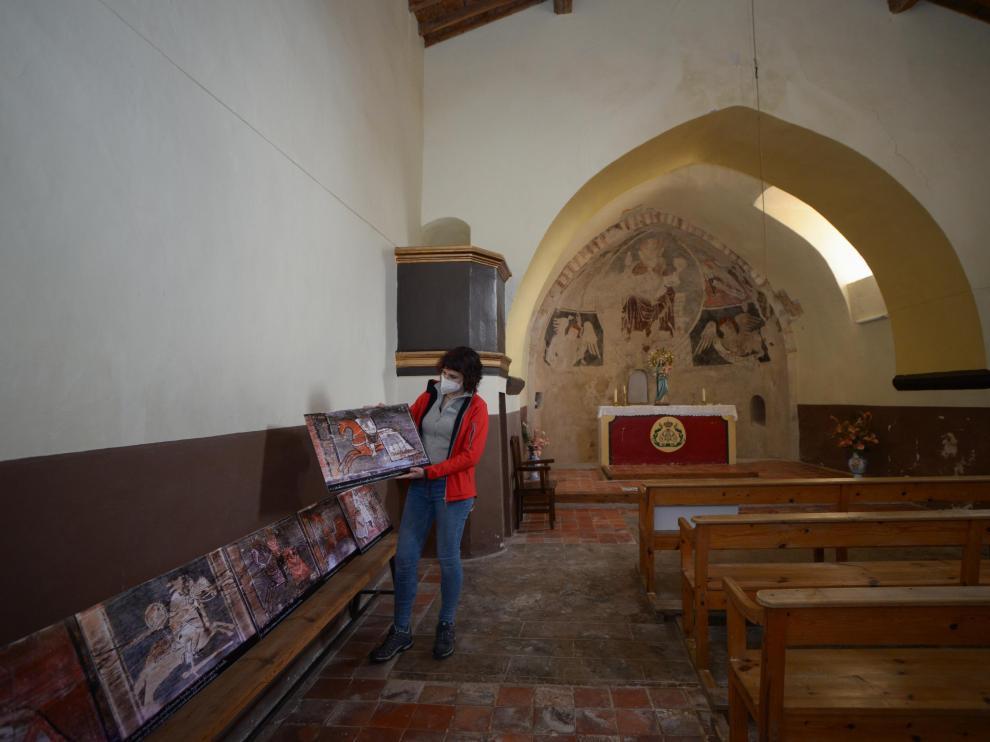 Sara Ros, en el interior de la ermita de Camañas, muestra reproducciones de la decoración de la techumbre.