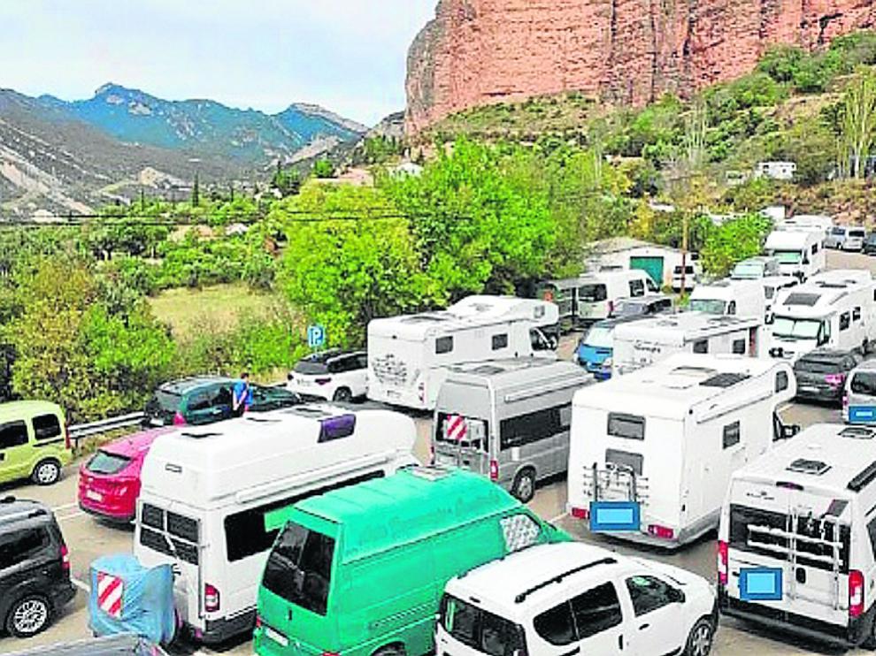 Zona de aparcamiento reservada para autobuses ocupada por turismos y caravanas en Riglos