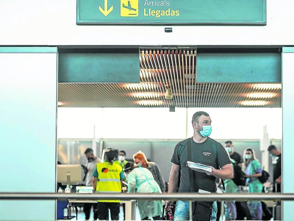 Viajeros procedentes de Rumanía y de Reino Unido, ayer, en el aeropuerto de Zaragoza