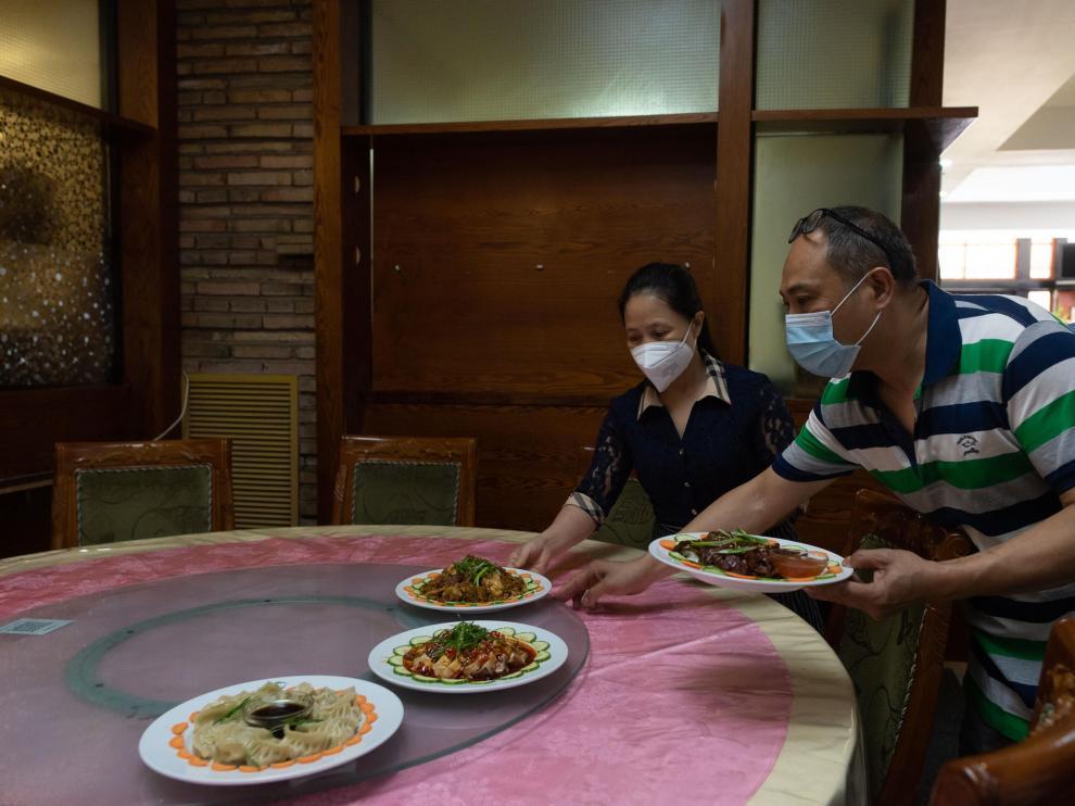 Xianping (en primer término) y Yong sirven platos en su restaurante Kilinke.