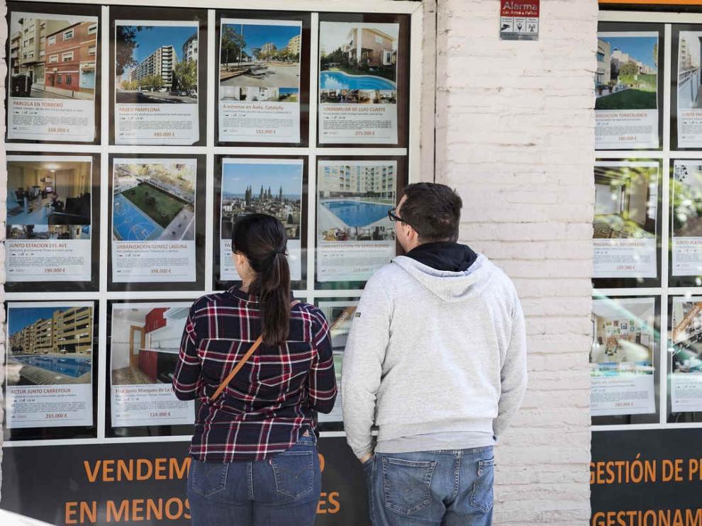 Jóvenes mirando ofertas de pisos en Zaragoza.