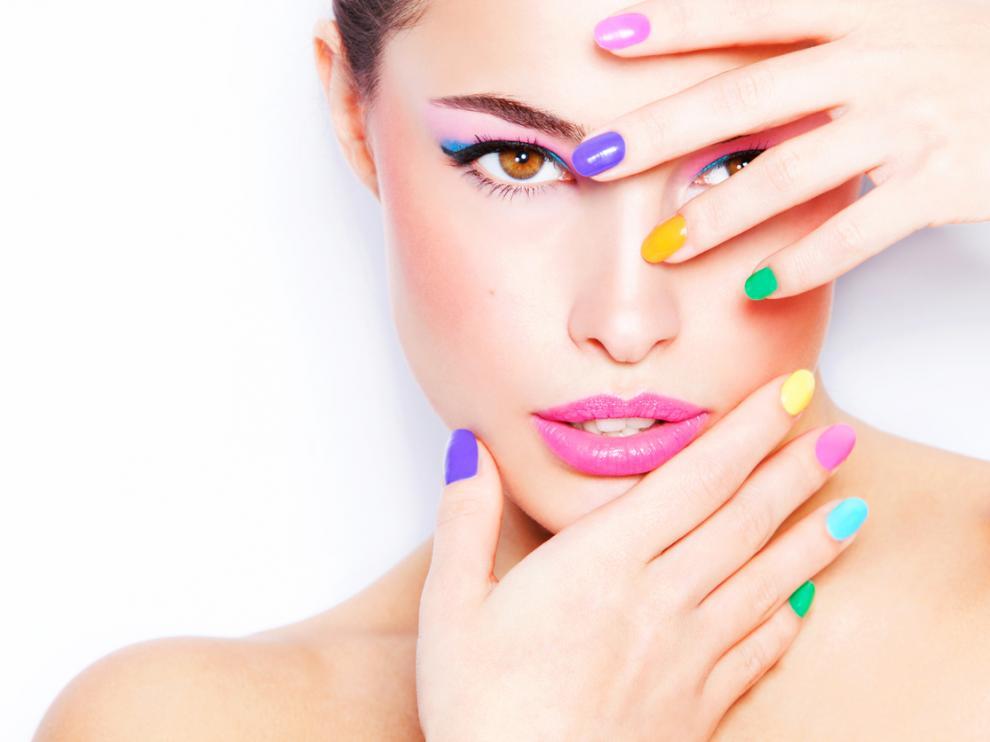 Mujer con manicura especial con uñas de colores distintos