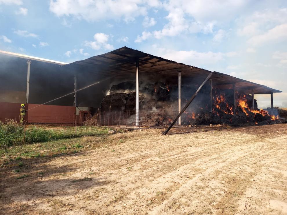 Los bomberos del parque de Barbastro han acudido a sofocar el incendio de la nave de paja de Bierge.