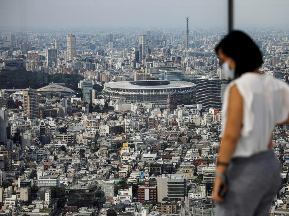 Una mujer con mascarilla observa el principal estadio de los Juegos Olímpicos.