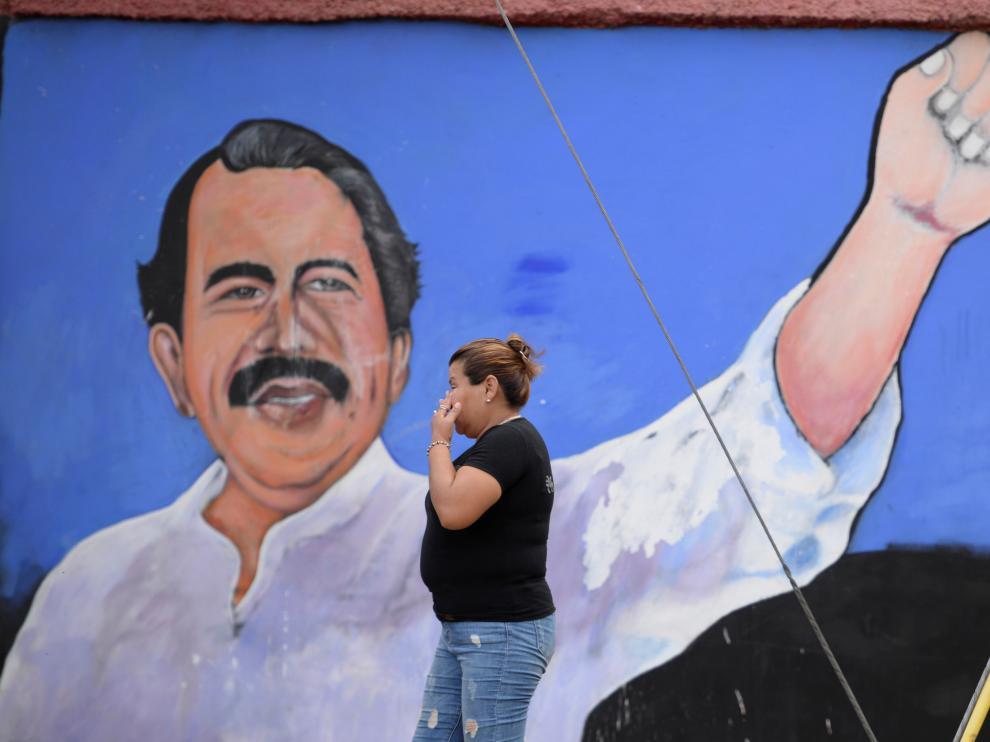 Una mujer pasa por un muro en el que está pintado Ortega.