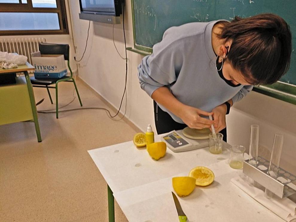 Una alumna del IES Valle del Ebro realiza experimentos para comprobar si el jugo del cítrico pierde sus vitaminas una vez exprimido