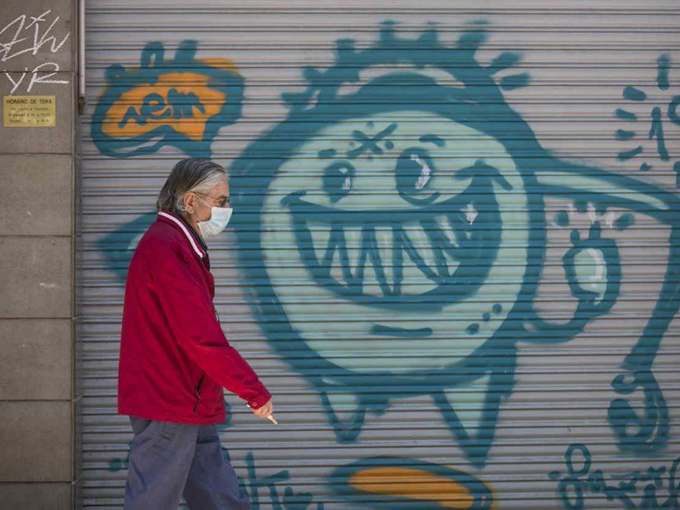 Un hombre protegido con mascarilla, frente a una pintada de la covid-19 en Zaragoza.