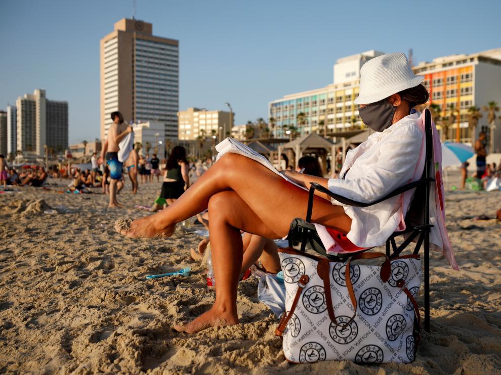 Una mujer con mascarilla en una playa cercana a Tel Aviv