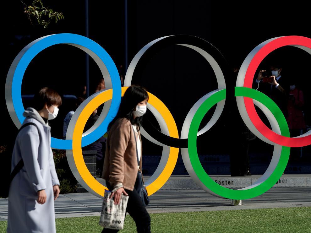 Una personas con mascarilla pasan por delante de los aros olímpicos en Tokio.