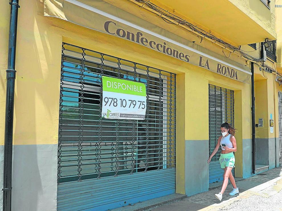 Locales comerciales cerrados en un tramo de la Ronda de Ambeles con el pavimento parcheado