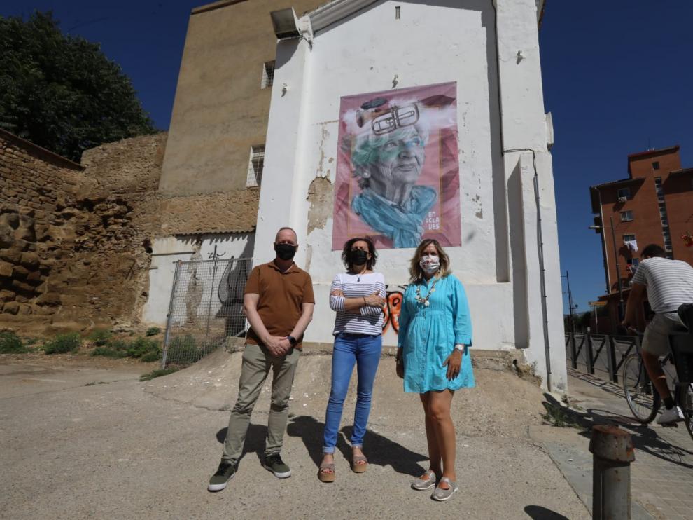 El concejal de Cultura de Huesca, Ramón Lasaosa, la fotógrafa Sol Montenegro y la consejera de Cultura de La Hoya, Beatriz Calvo, delante de la imagen del Festival Enclaves, colocada en el Trasmuro de Huesca.