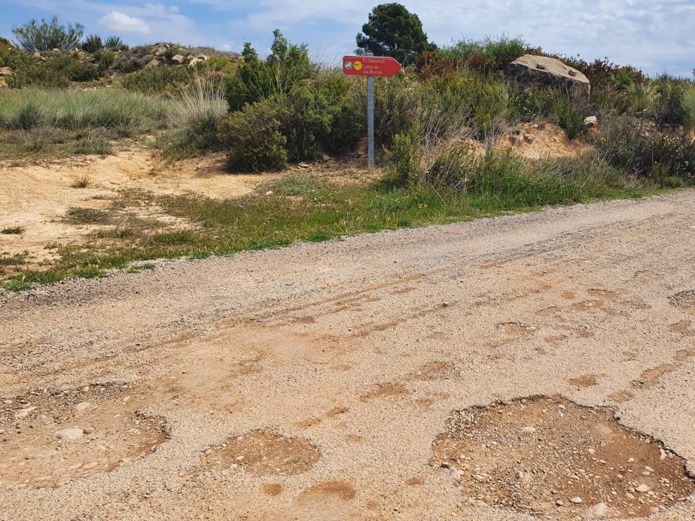 Una señal informa de la proximidad del yacimiento arqueológico de El Cascarujo en la pista que conduce al embalse de Civán desde Alcañiz.