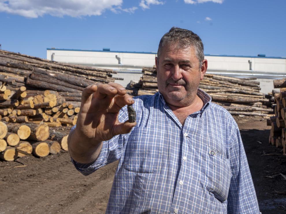 Mateo Bielsa muestra un trozo de metralla hallado en los troncos que llegan a su serrería de Teruel.