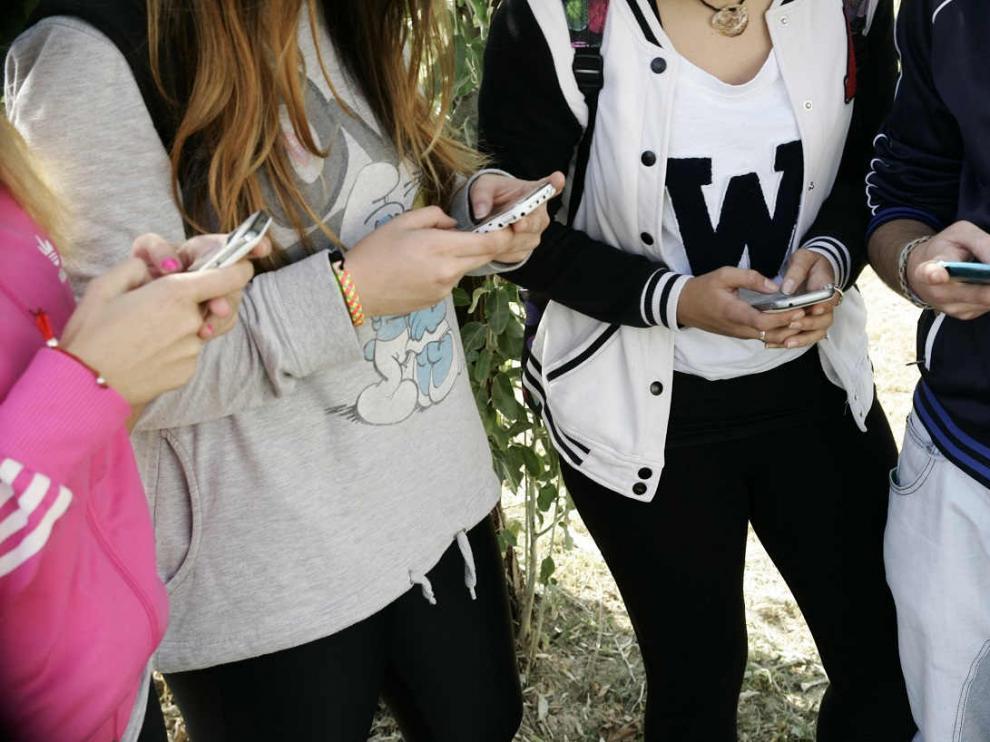 Un grupo de adolescentes reunidos con sus móviles.