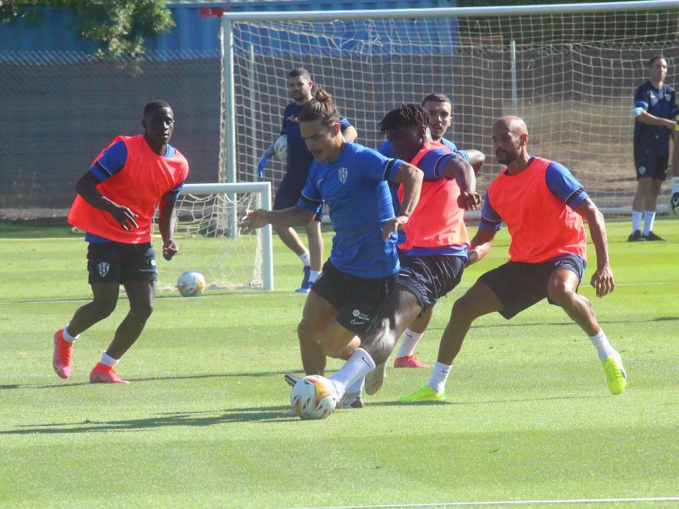 Ronald y Mikel Rico defienden a Seoane durante el entrenamiento de la SD Huesca de este viernes.