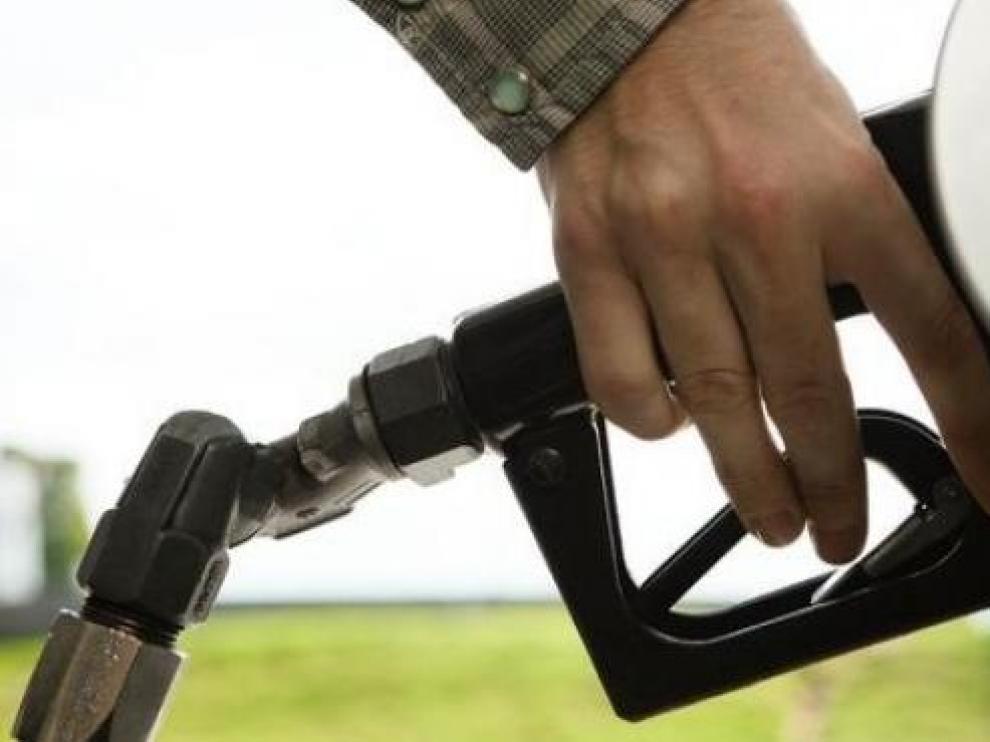 Una persona echando combustible en una gasolinera.