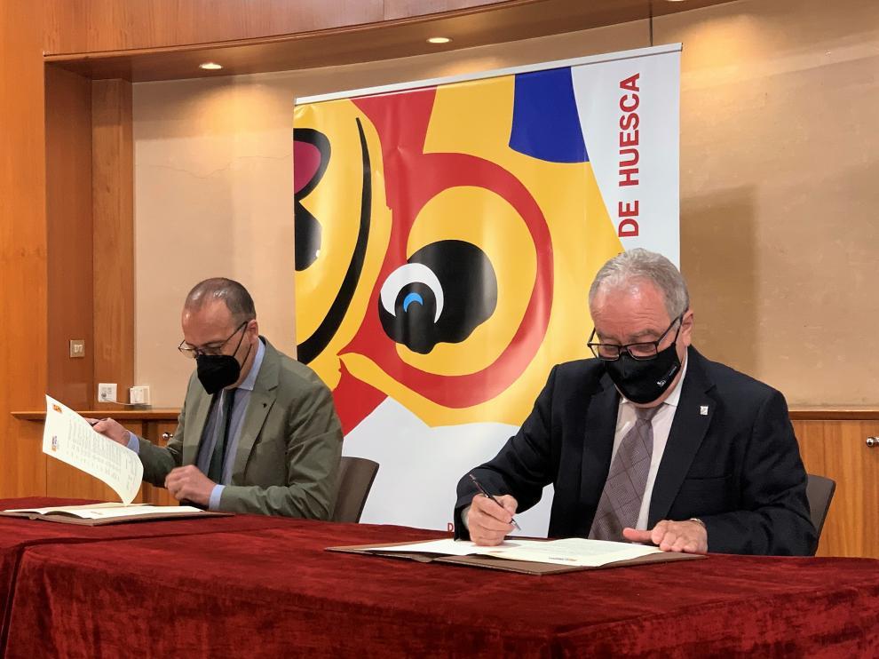 El consejero de Educación, Felipe Faci (i), y el presidente de la DPH, Miguel Gracias, durante la firma del convenio.