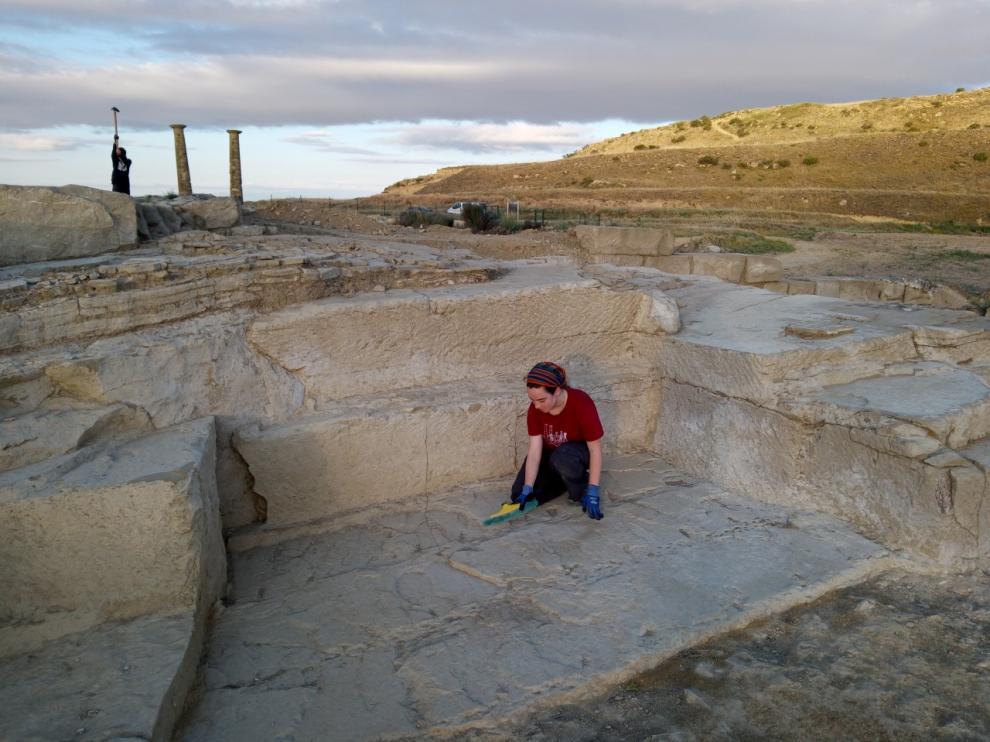 Una estudiante que participa en la excavación limpia los restos de la cantera de piedra encontrada en Los Bañales.