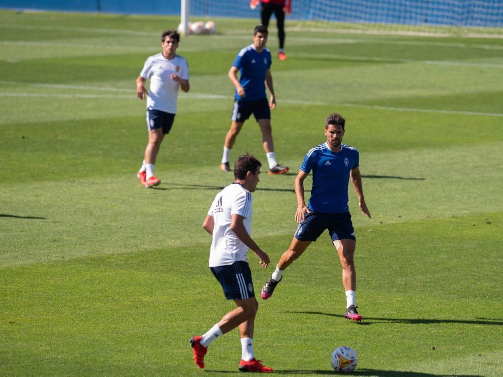 Zapater lleva la pelota ante Adrián González, ante la mirada de Iván Azón y      en el partido de entrenamiento jugado por el Real Zaragoza en la mañana de este miércoles en La Romareda.