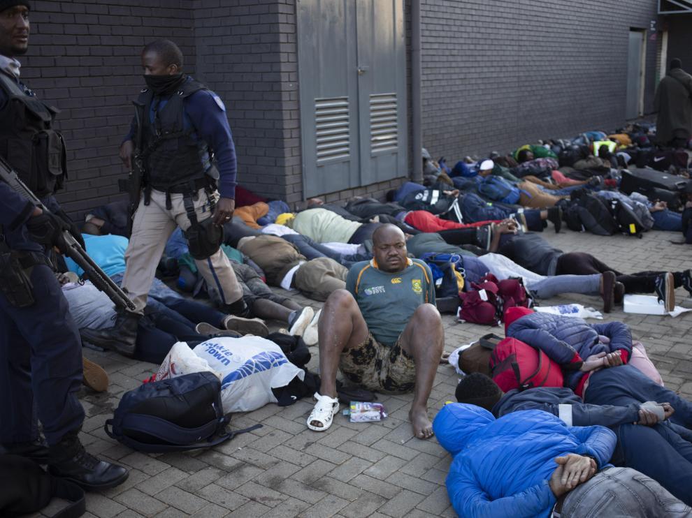 Decenas de personas tendidas en el suelo bajo arresto en Sudáfrica
