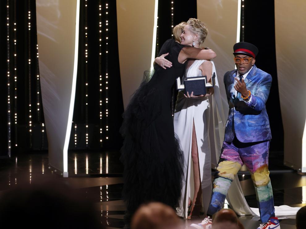 La directora Julia Ducournau abraza a Sharon Stone en presencia de Spike Lee.