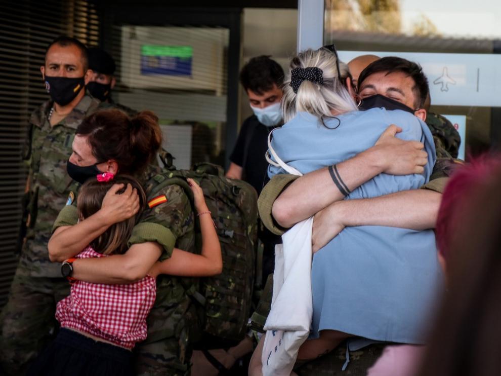 Dos militares de la Brigada Aragón saludan a sus familiares en el aeropuerto de Zaragoza.