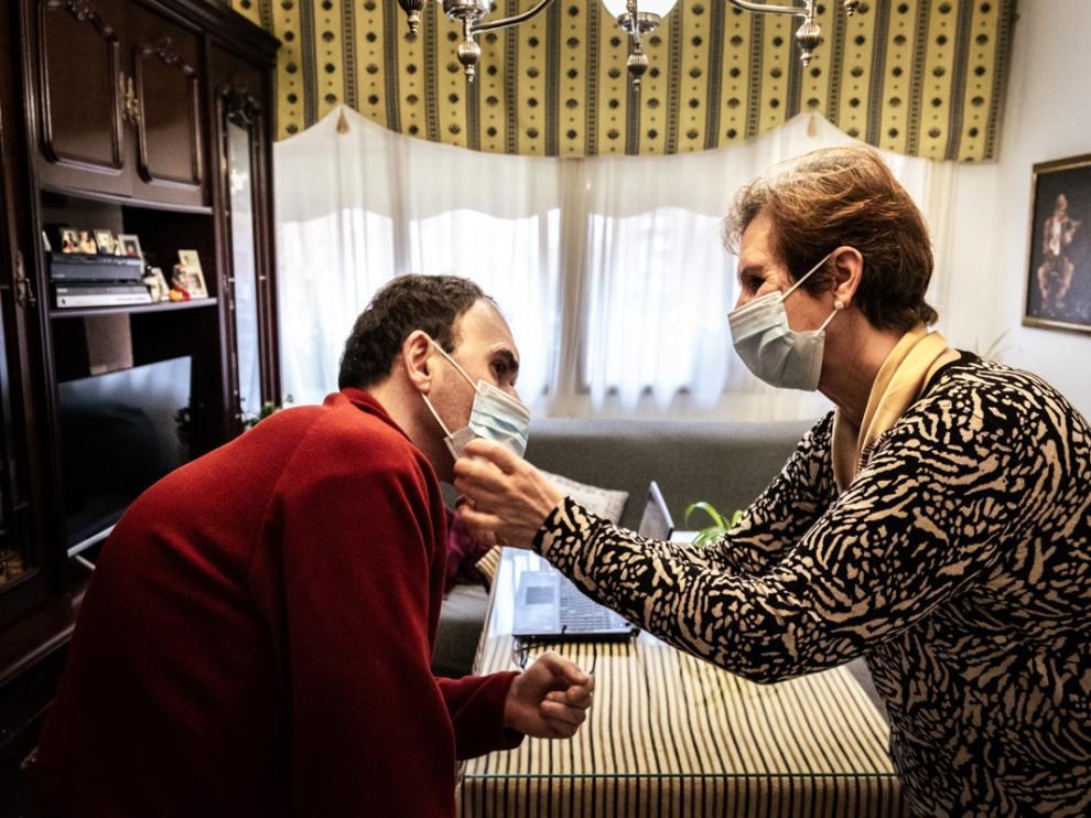 Una mujer ayuda a su hijo con discapacidad a colocarse la mascarilla.ROBERTO PALOMO   (Foto de ARCHIVO) 11/2/2021