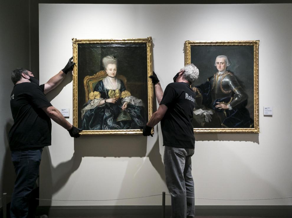 Dos operarios cuelgan el segundo de los retratos en su emplazamiento actual, en la Sala Goya del museo.