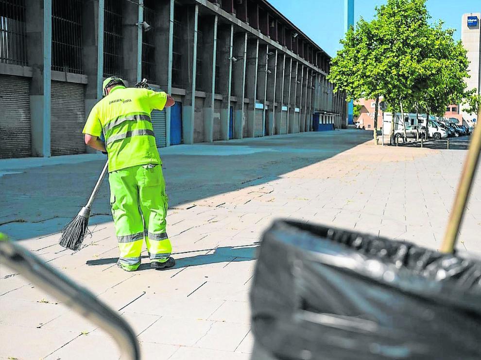 Un operario de limpieza barre el suelo junto al estadio de La Romareda, ayer.