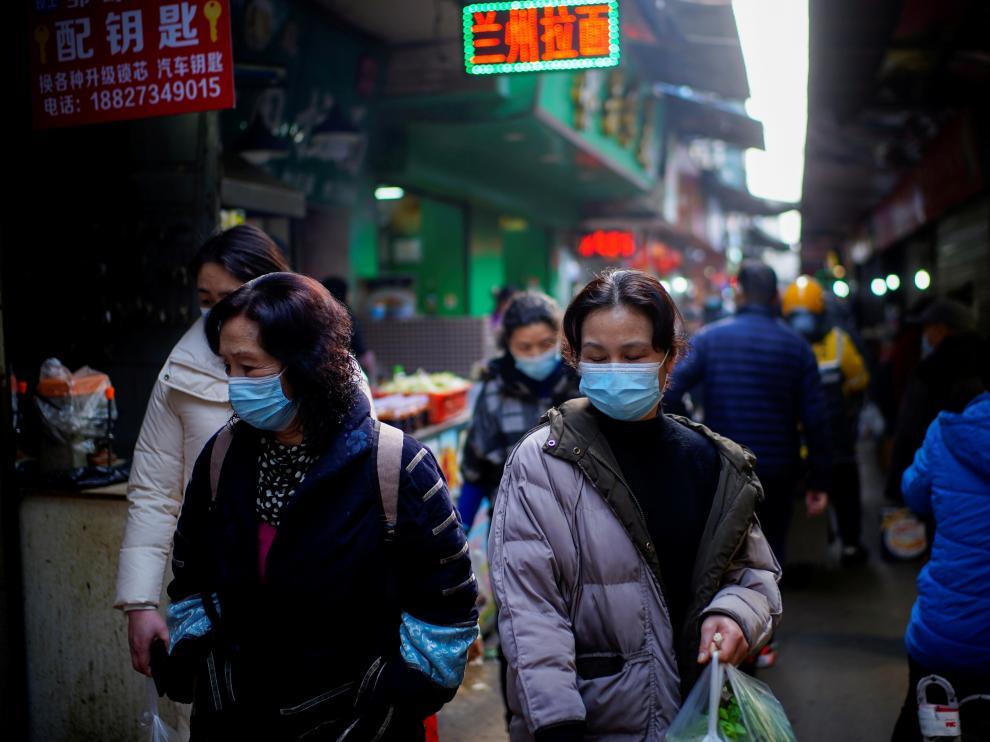 Gente con mascarillas por la calle del mercado de Wuhan donde arrancó la pandemia