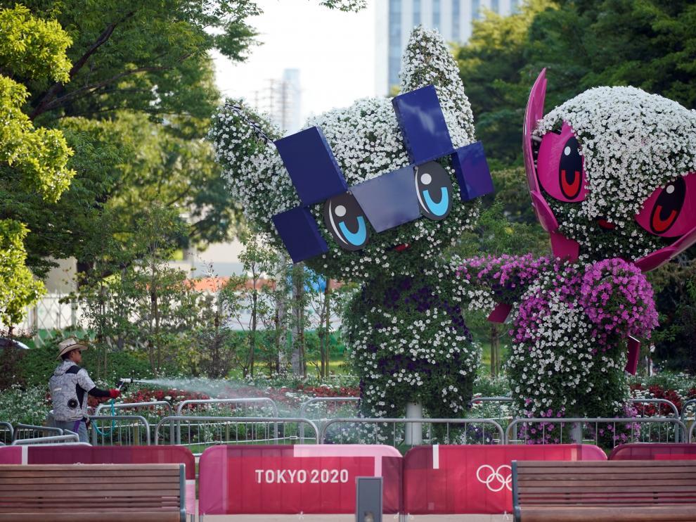 Un jardinero riega las reproducciones de las mascotas de los Juegos de Tokio