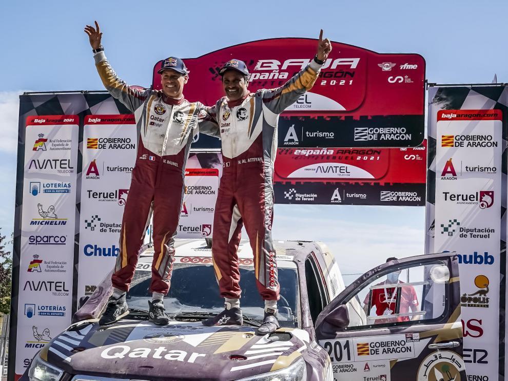 Al-Attiyah celebra el triunfo en la Baja Aragón subido en su coche con su copiloto, Baumel.