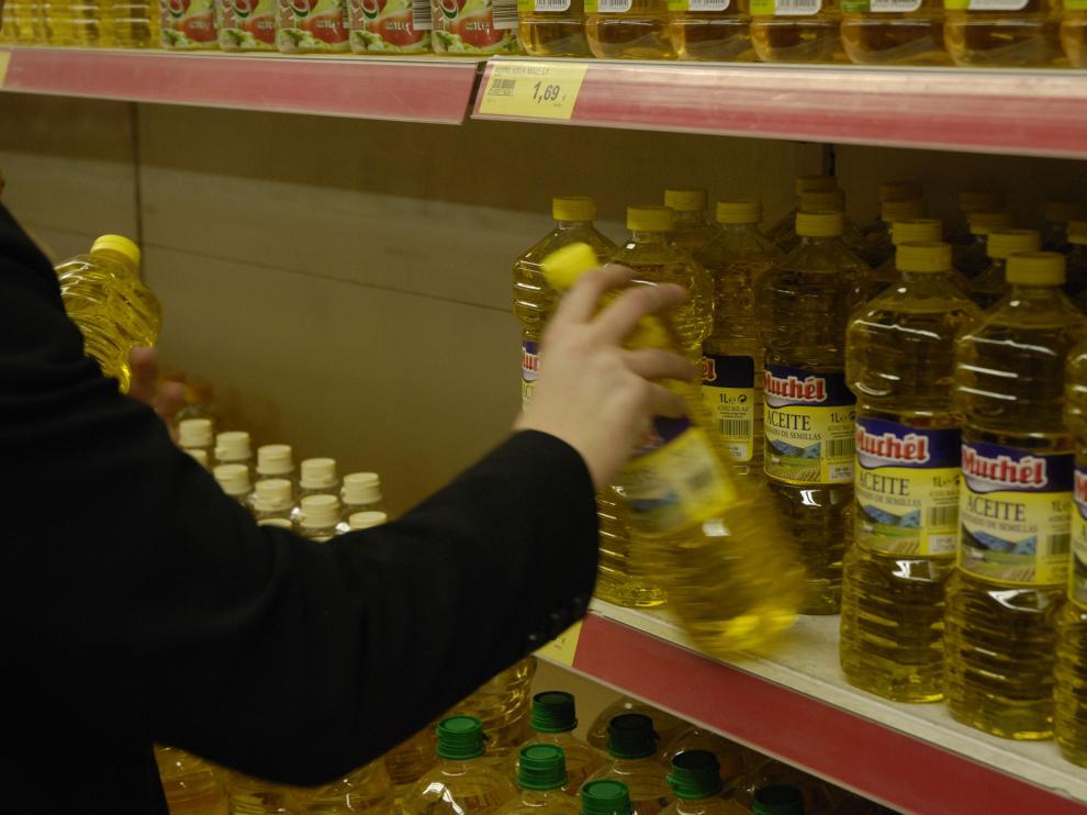 Imagen de archivo de una estantería con botellas de aceite en un supermercado,