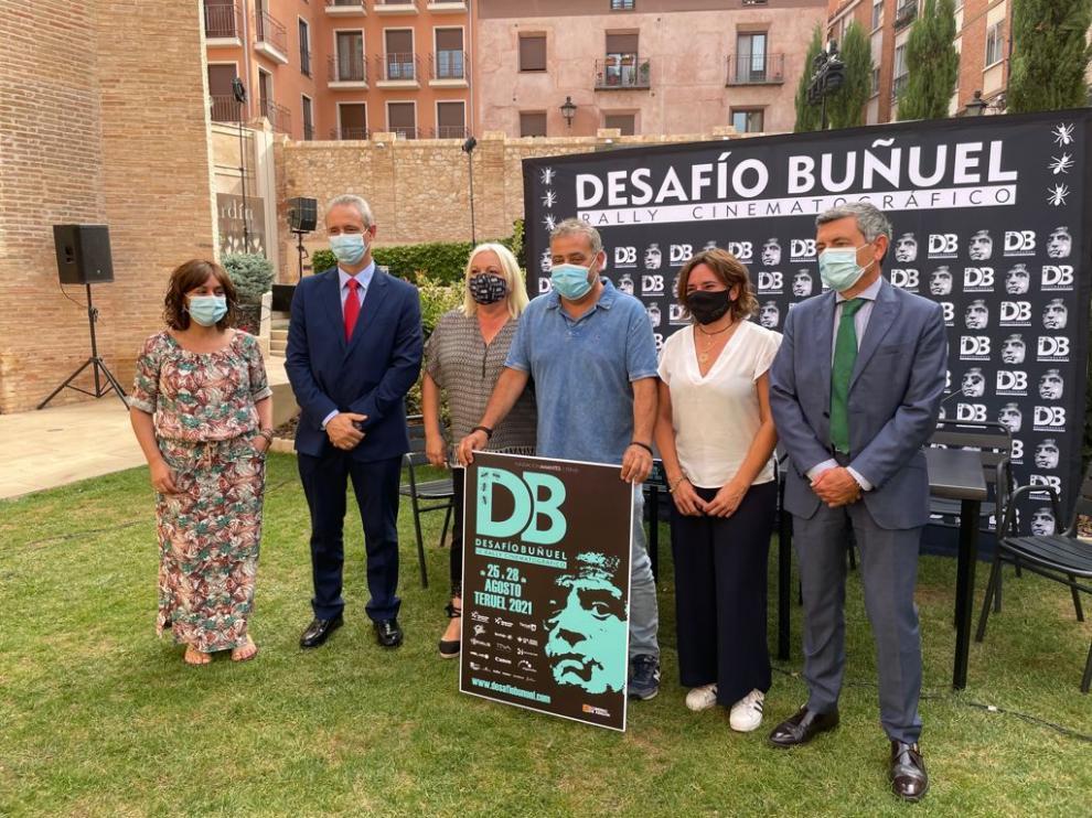 Pimpi López, director del Rally, sostiene el cartel del Desafío Buñuel junto al resto de patrocinadores.