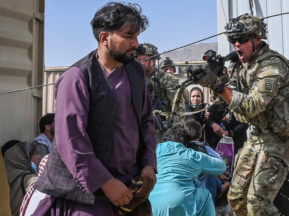Un soldado estadounidense apunta a un hombre en el aeropuerto de Kabul.