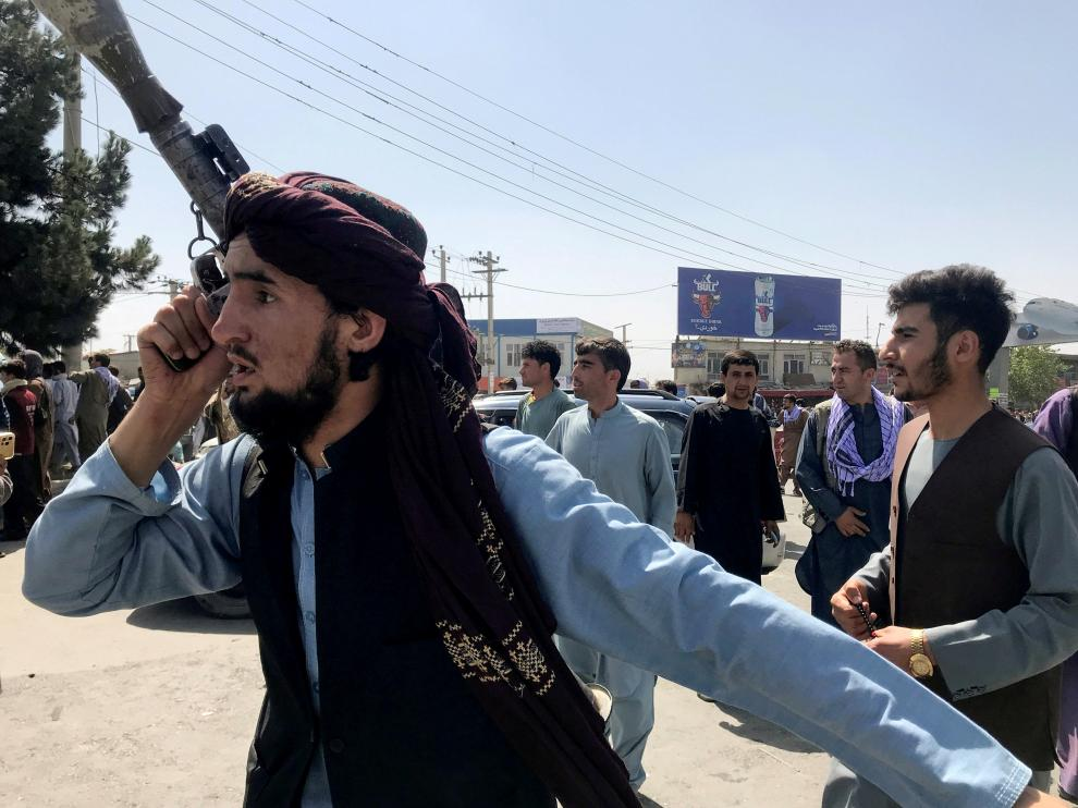 FILE PHOTO: A member of Taliban forces inspects the area outside Hamid Karzai International Airport in Kabul