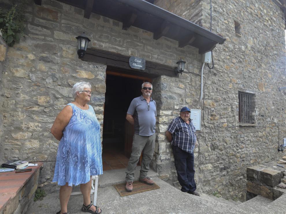 El alcalde de Tella-Sin, Feliciano Sesé, en el centro, junto a dos de los vecinos de Revilla, que recientemente ha celebrado la llegada de la luz.