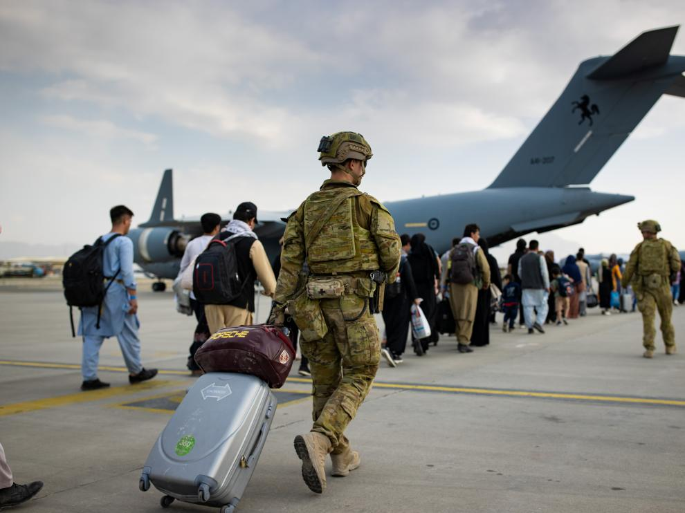 Australian citizens and visa holders prepare to board the Royal Australian Air Force C-17A Globemaster III aircraft, as Australian Army infantry personnel provide security and assist with cargo, at Hamid Karzai Internati
