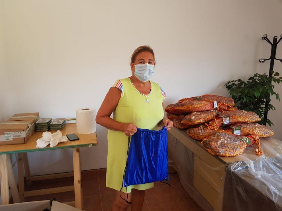 Pilar Molina, alcaldesa de Allueva, junto a los jamones que se han regalado a sus vecinos.