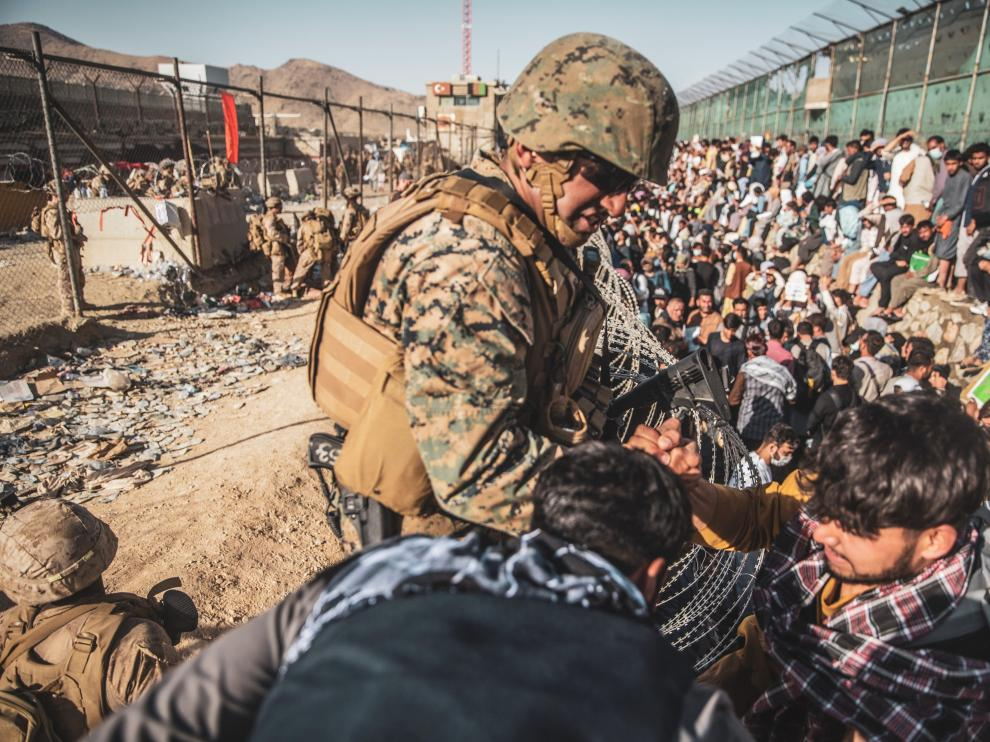 A U.S. Marine assists at an Evacuation Control Check Point (ECC) during an evacuation at Hamid Karzai International Airport, Kabul, Afghanistan, August 26, 2021. Picture taken August 26, 2021.  U.S. Marine Corps/Staff Sgt. Victor Mancilla/Handout via REUTERS.  THIS IMAGE HAS BEEN SUPPLIED BY A THIRD PARTY.[[[REUTERS VOCENTO]]] AFGHANISTAN-CONFLICT/