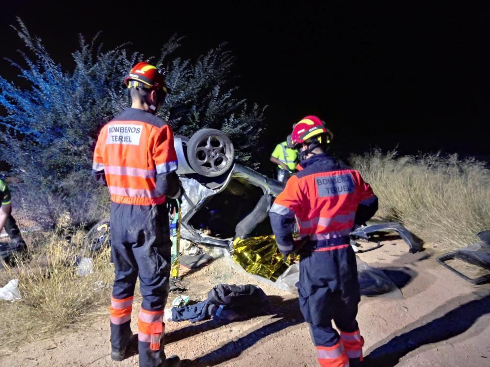 Los Bomberos de Teruel, junto al vehículo volcado.