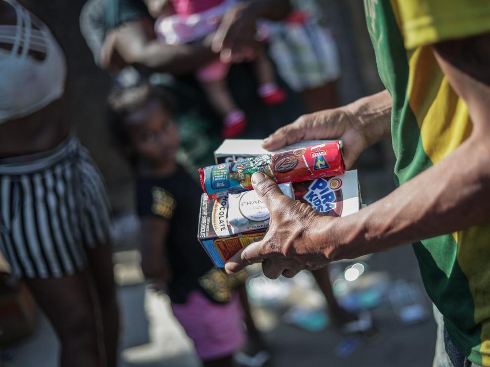 Un hombre recibe alimentos por parte de voluntarios de la eoenegé Covid Sem Fome en un barrio de Río de Janeiro, en Brasil.