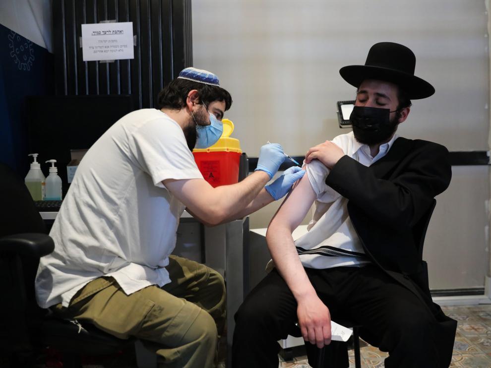 Un enfermero israelí inocula con la tercera dosis de la vacuna a un ciudadano