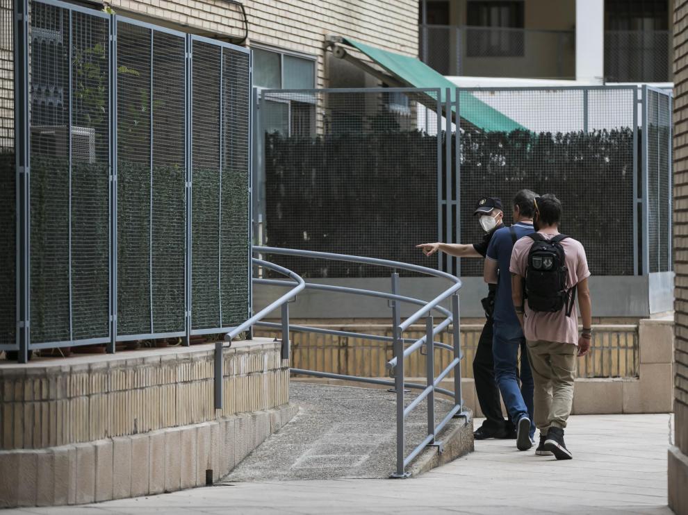 Tres agentes entran en el portal de la vivienda donde ocurrió la agresión.
