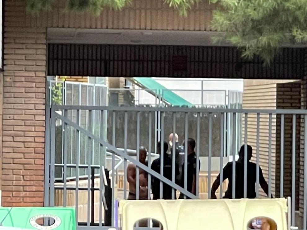 A la izquierda, el detenido por acuchillar a su compañero de piso es conducido por la Policía.