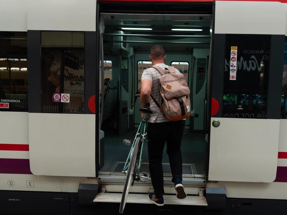 Un ciclista accede a un tren de la línea de Cercanías Casetas-Miraflores.