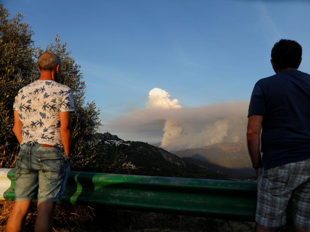 Dos personas observan uno de los pyrocúmulos  generados por el incendio de Sierra Bermeja en Málaga.