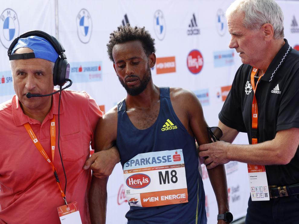 Derara Hurisa, agotado, es ayudado tras acabar el maratón de Viena, del que fue después descalificado.