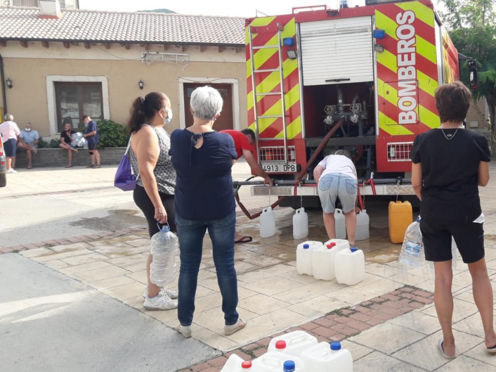 Vecinos de Laguarres hacen cola para llenar de agua sus garrafas en el camión de bomberos.